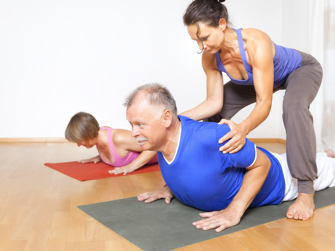 Personal trainer helps two clients exercise for stress management.